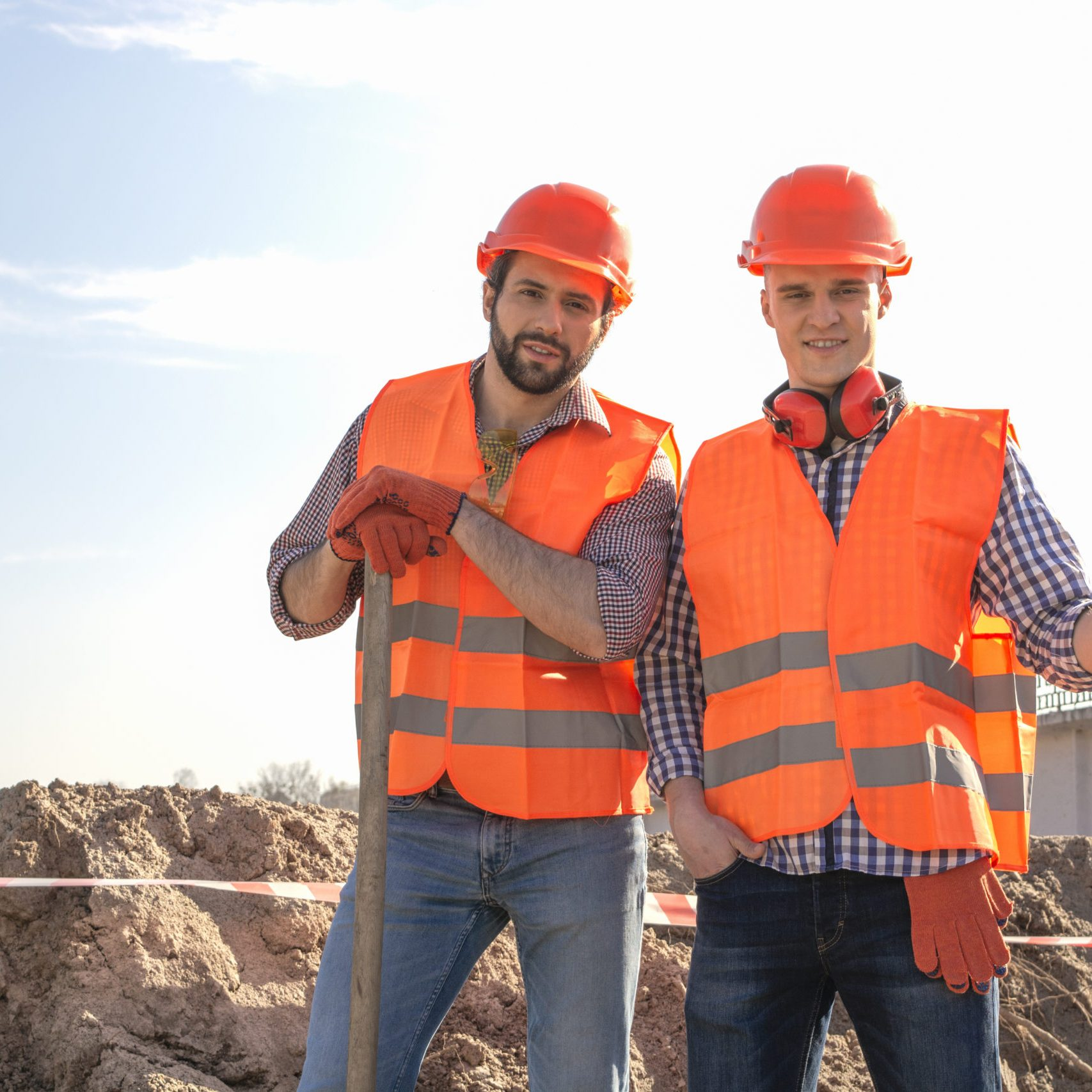 male workers engineers in helmets with the head, work, in the hands of a shovel